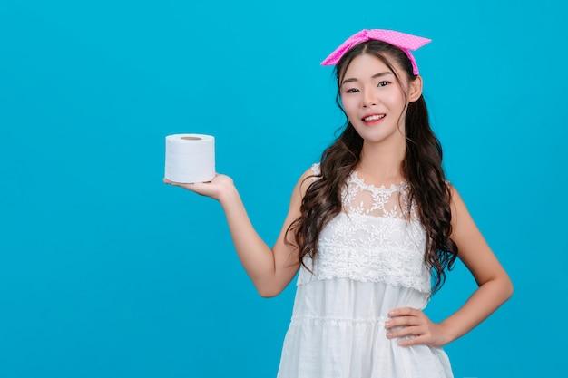 Tragende weiße pyjamas des mädchens, die eine rolle des seidenpapiers in der hand auf dem blau halten.