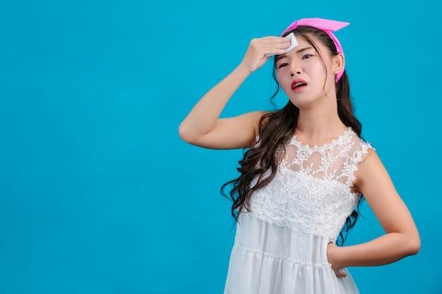 Tragende weiße pyjamas des mädchens unter verwendung des seidenpapiers auf ihrem gesicht auf einem blau.
