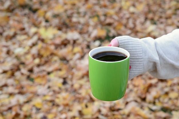 Tragende weiße strickjacke der frau, die eine rohkaffeetasse hält