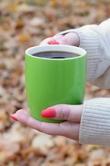 Tragende weiße strickjacke der frau, die kaffeetasse hält