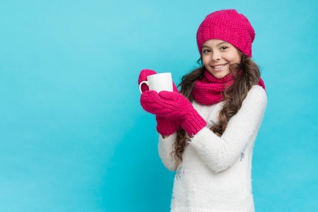 Tragende winterkleidung des mädchens und halten der teeschale