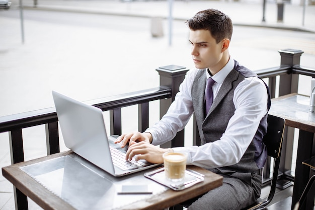Tragender anzug des hübschen geschäftsmannes und modernen laptop draußen verwenden