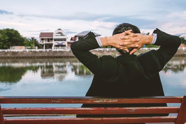 Tragender anzug des mannes, der auf parkbank sitzt