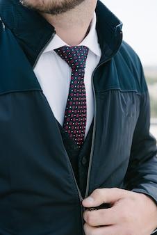 Tragender anzug des mannes und bindungsaufstellung. werbung für herrenbekleidung.