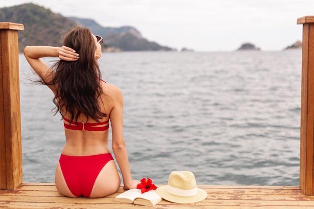Tragender badeanzug der frau, der auf dock steht