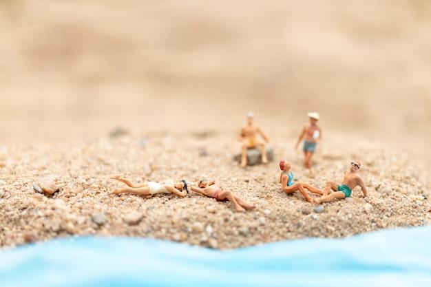 Tragender badeanzug der miniaturleute, der auf dem strand sich entspannt
