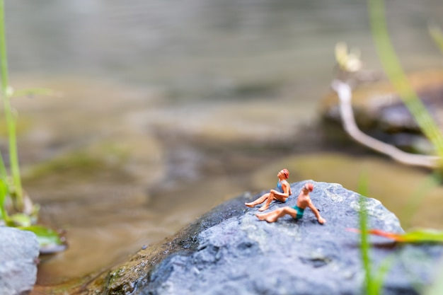Tragender badeanzug der miniaturleute, der auf einem felsen ein sonnenbad nimmt