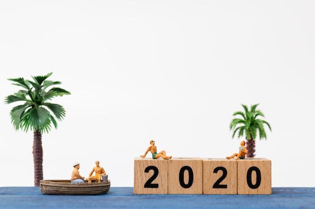 Tragender badeanzug der miniaturleute, der das sitzen auf holzklotz nr. 2020 sich entspannt