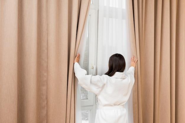 Tragender bademantel der frau im hotelzimmer