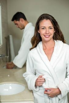 Tragender bademantel der jungen paare im badezimmer
