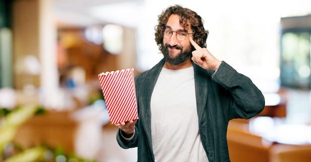 Tragender bademantennachtanzug des jungen mannes mit popcorneimer