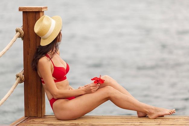 Tragender bikini der frau, der meer betrachtet