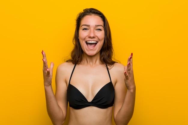 Tragender bikini der jungen europäischen frau, der einen sieg oder einen erfolg feiert