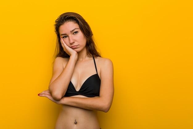 Tragender bikini der jungen europäischen frau, der gelangweilt, ermüdet ist und einen entspannungstag benötigt.