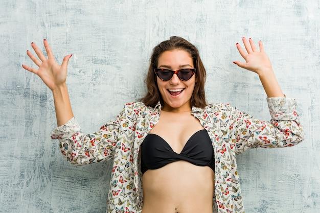 Tragender bikini der jungen europäischen frau, der wegen einer bevorstehenden gefahr entsetzt wird