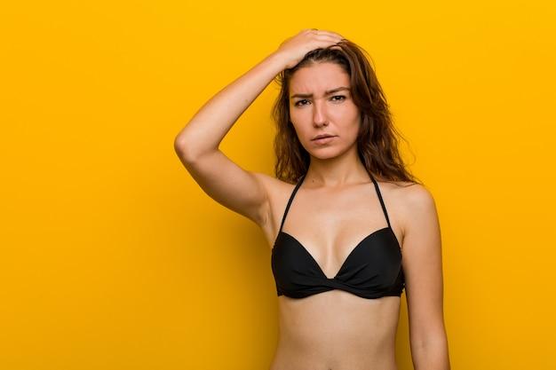 Tragender bikini der jungen europäischen frau ermüdete und sehr schläfrig, ihre hand auf ihrem kopf halten.