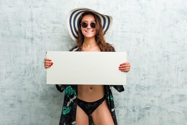 Tragender bikini der jungen europäischen frau und halten eines plakats