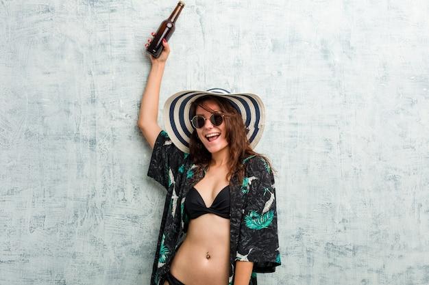 Tragender bikini der jungen europäischen frau und trinken eines bieres