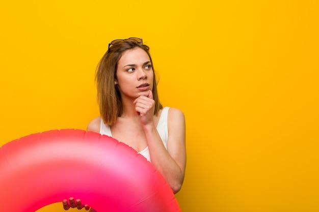 Tragender bikini der jungen frau, der einen aufblasbaren donut seitlich schaut mit zweifelhaftem und skeptischem ausdruck hält.