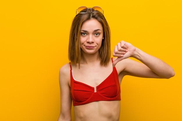 Tragender bikini und sonnenbrille der jungen kaukasischen frau, die eine abneigungsgeste, daumen unten zeigen. uneinigkeit konzept.
