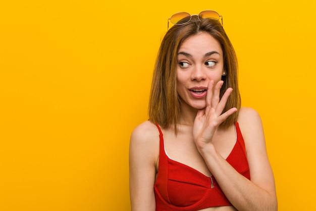 Tragender bikini und sonnenbrille der jungen kaukasischen frau sagt geheime heiße bremsennachrichten und schaut beiseite