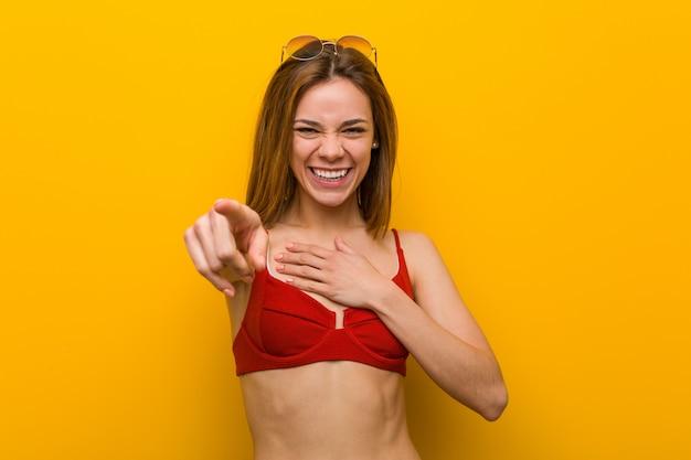 Tragender bikini und sonnenbrille der jungen kaukasischen frau zeigt mit dem daumenfinger weg, lachend und sorglos.