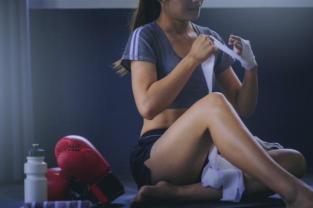 Tragender bügel des boxers der jungen frau auf dem handgelenk bereit zur boxübung.