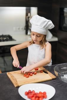 Tragender chefhut und -schutzblech des kleinen mädchens, die tomaten auf hackendem brett in der küche schneiden