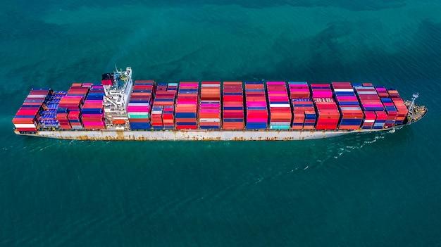 Tragender containerkasten des frachtfrachtschiffs für import- und exportgeschäftslogistik und transport durch frachtschiff in der hohen see, vogelperspektive.