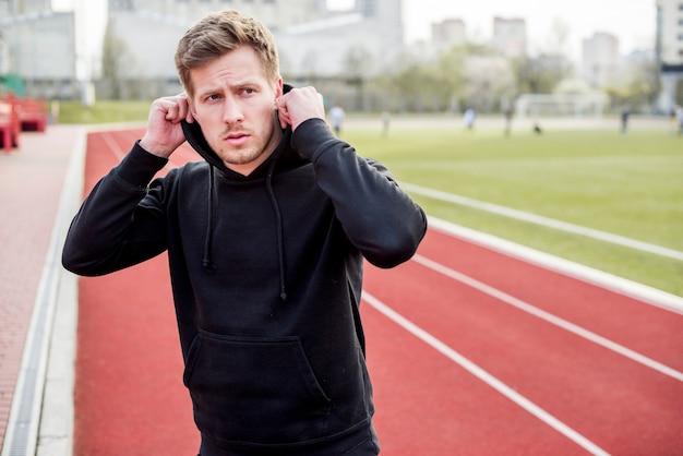 Tragender hoodie des hübschen sportmannes auf rennstrecke