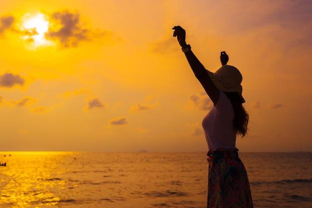 Tragender hut der frau mit den armen hob stellung auf seestrand bei sonnenuntergang an
