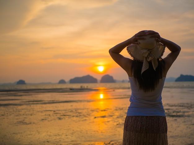 Tragender hut der frau mit den offenen armen unter dem sonnenaufgang nahe dem meer.