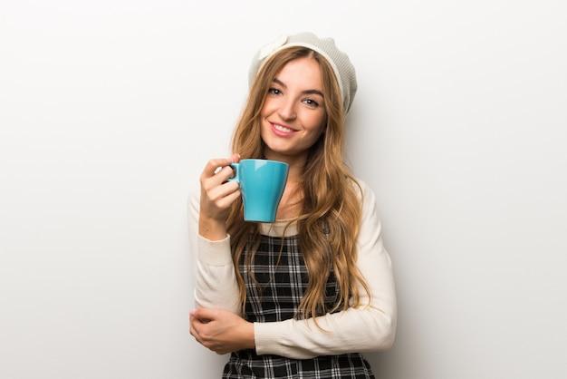 Tragender hut der modern frau, der einen heißen tasse kaffee hält