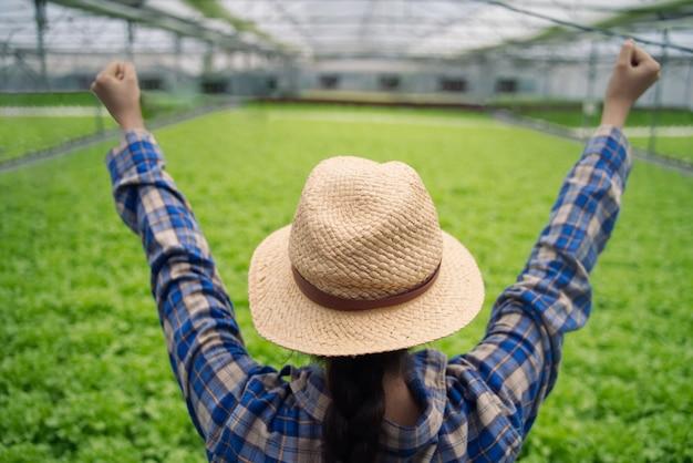 Tragender hut des asiatischen landwirtmädchens, der im grünen haus der hydrokultur arbeitet.