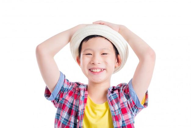 Tragender hut und lächeln des jungen asiatischen jungen über weißem hintergrund