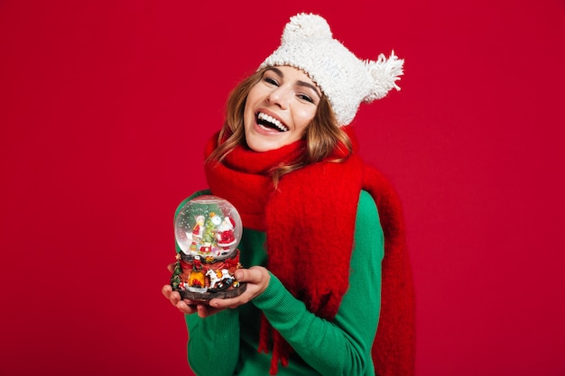 Tragender hut und schal junger hübscher dame, die weihnachtsspielzeug halten