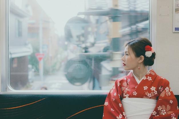 Tragender kimono der asiatin, der durch den klassischen zug japans sitzt nahe dem fenster reist
