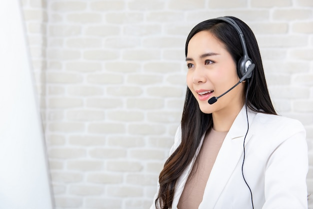 Tragender kopfhörer der schönen asiatischen geschäftsfrau, der in call-center arbeitet