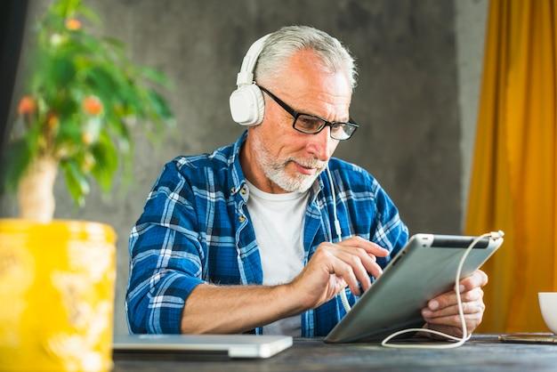 Tragender kopfhörer des älteren mannes unter verwendung der digitalen tablette