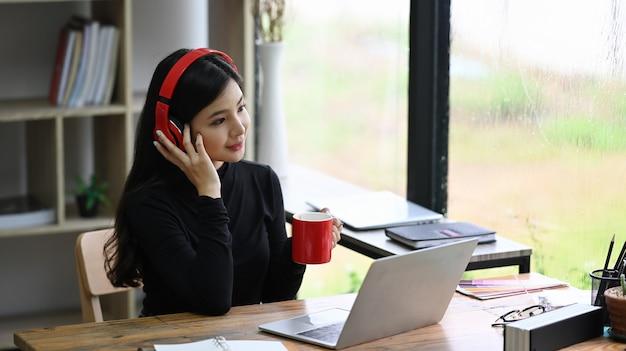 Tragender kopfhörer des attraktiven designers der jungen frau und trinkender kaffee im büro.