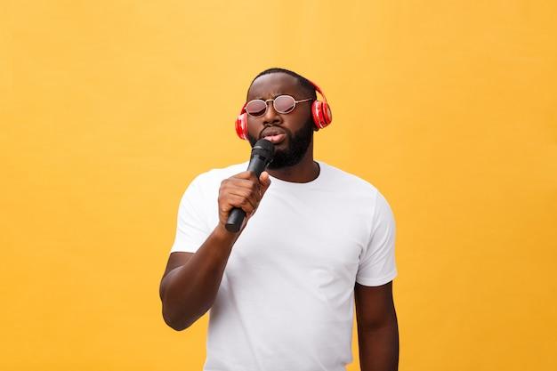 Tragender kopfhörer des jungen afroamerikanermannes und genießen musik über hintergrund des gelben goldes