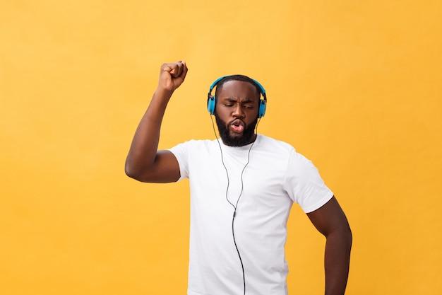 Tragender kopfhörer des jungen afroamerikanermannes und genießen sie die musik, die über gelbes goldhintergrund tanzt
