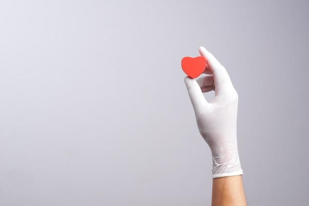 Tragender latexhandschuh der hand, der hölzernen herzformgegenstand hält