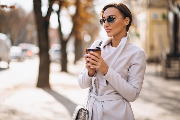 Tragender mantel der frau und trinkender kaffee