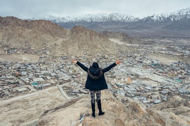 Tragender mantel des jungen asiatischen frauenreisenden, der die ansicht von leh ladakh-stadt in leh, ladakh, indien genießt.