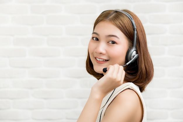 Tragender mikrofonkopfhörer der zufälligen asiatischen geschäftsfrau als telemarketing-kundendienstmitarbeiter