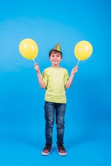 Tragender partyhut des glücklichen jungen, der ballone im blauen hintergrund hält