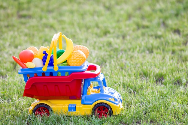 Tragender plastikkorb des bunten spielzeugauto-lkws mit spielzeugobst und gemüse draußen am sonnigen sommertag.