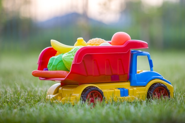 Tragender plastikkorb des bunten spielzeugauto-lkws mit spielzeugobst und gemüse