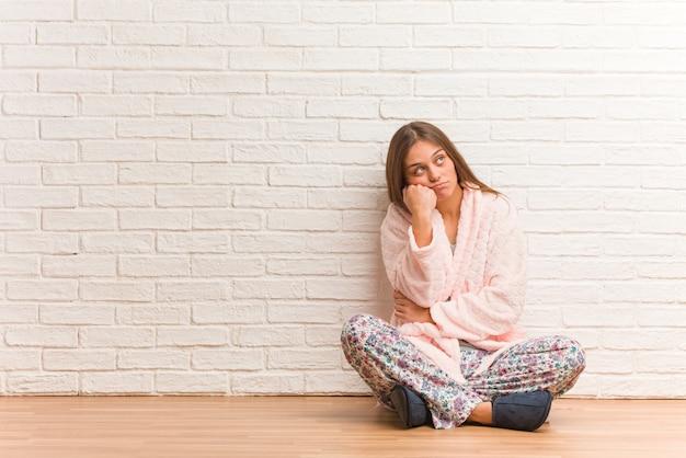 Tragender pyjama der jungen frau, der an etwas, schauend zur seite denkt